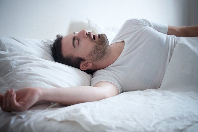 Man-sleeping-in-his-bed-and-snoring-loudly-640x426