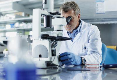scientist-looking-through-microscope-487041749-58d5504a5f9b584683dc6de6