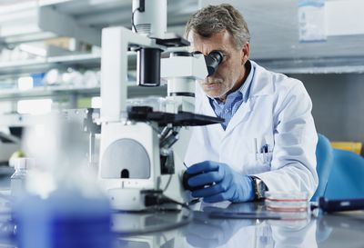 scientist-looking-through-microscope-487041749-58d5504a5f9b584683dc6de6