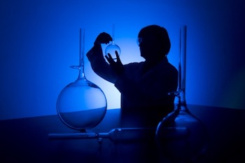10133712 - silhouette of a female researcher carrying out research in a chemistry lab